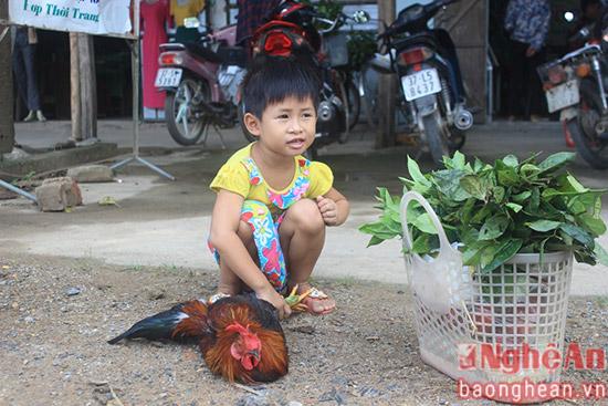 Một em bé giữ chặt con gà và ngồi trông đồ cho mẹ tiếp tục vào chợ.