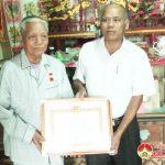 Đồng chí Trương Hồng Phúc – Bí thư huyện uỷ trao huy hiệu  70 năm tuổi Đảng cho ông Hoàng Văn Thận